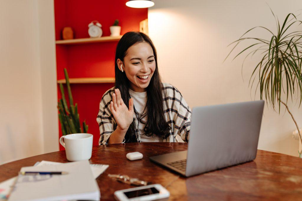 Positive girl in wireless headphones speaks by video link in laptop